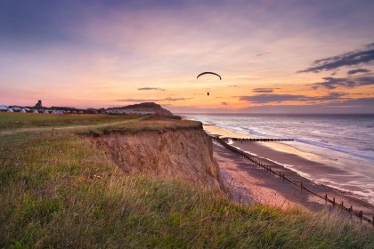 Paragliders on the Norfolk coast at sunset