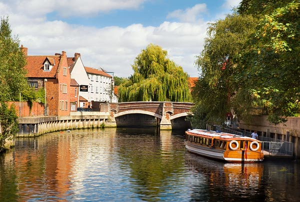A boat travels down the River Wensum in Norwich